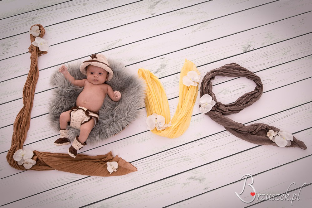 Newborn posing with a LOVE word